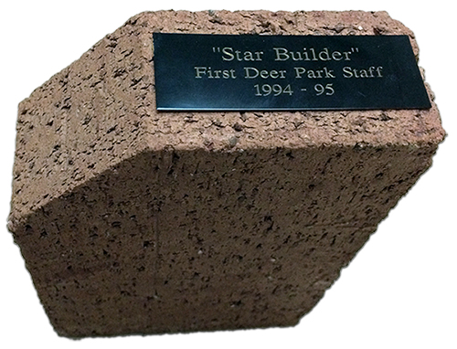 Photograph of the brick doorstop described by Donna Ford. The color is a light reddish-brown. A small plaque, affixed to the top, reads Star Builder, First Deer Park Staff, 1994 to 1994. The brick is pentagonal, not rectangular, in shape.