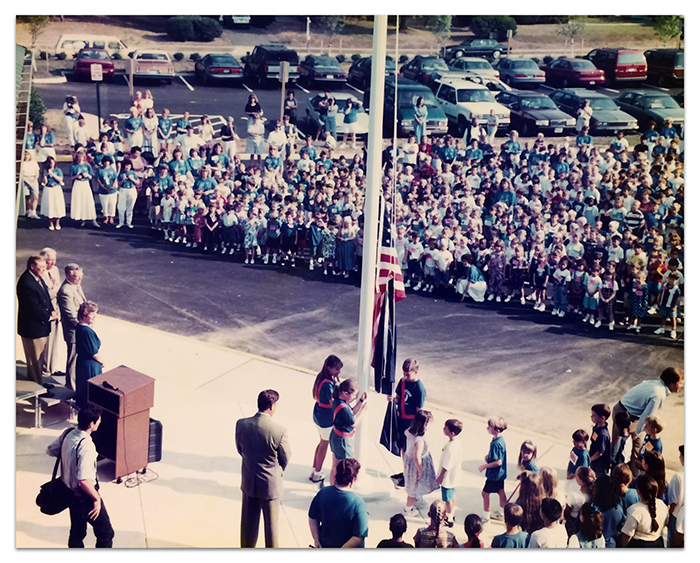 Color photograph taken from the roof of Deer Park Elementary School during its dedication ceremony. We are looking down at a crowd of students gathered in front of the school as another group of students is participating in a flag raising ceremony.